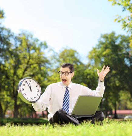 Young angry businessperson with laptop sitting on green grass and looking at clock in a park, shot with a tilt and shift lens photo