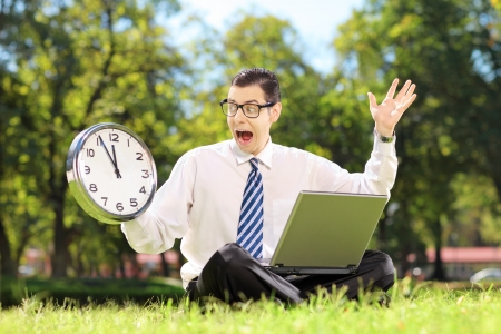 Young angry businessperson with laptop sitting on green grass and looking at clock in a park photo