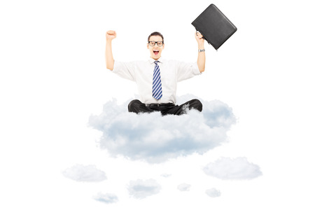 Young happy businessman with suitcase riding on clouds isolated on white background photo