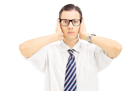 Young man with glasses covering his ears with hands isolated on white background photo