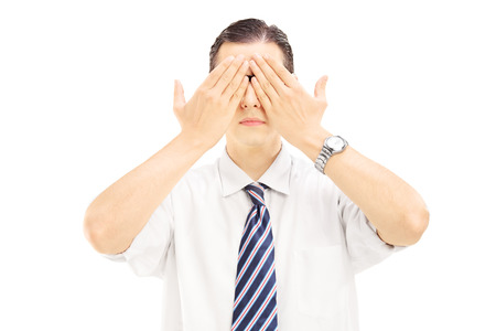 hand covering eye: Young man with hands over his eyes isolated on white background