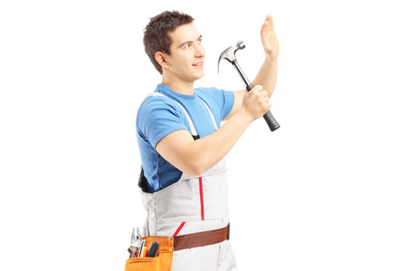 Male manual worker working with hammer isolated against white background Stock Photo