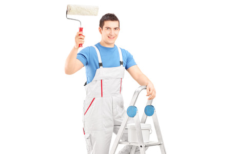 Male painter holding a roller and standing on a ladder isolated on white background photo