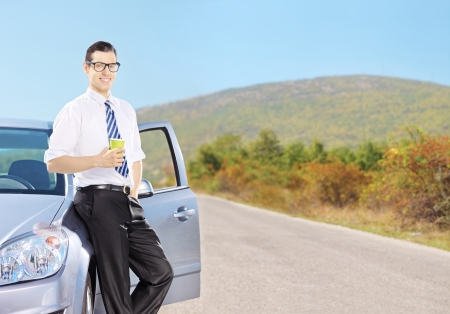 tar paper: Smiling young man on his automobile relaxing and drinking coffee on an open road, shot with a tilt and shift lens