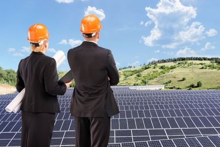 Team of architects examining solar panels under sunny sky, Macedonia photo