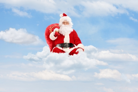 Santa Claus sitting on clouds holding a bag  photo