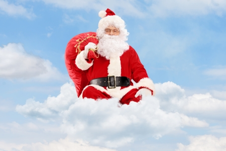 Santa Claus seated on clouds holding a bag and flying photo