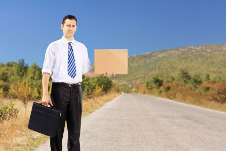 Young businessman holding a leather suitcase and hitchhiking on an open road photo