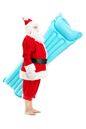 Full length portrait of a Santa claus holding a swimming mattress on vacation, isolated on white
