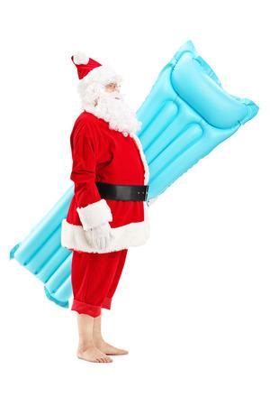 ropa de verano: Retrato de cuerpo entero de un Santa claus sosteniendo un colchón de la natación de vacaciones, aislado en blanco