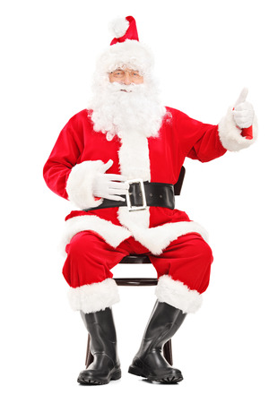 Happy Santa claus sitting on a wooden chair and giving a thumb up isolated on white  photo