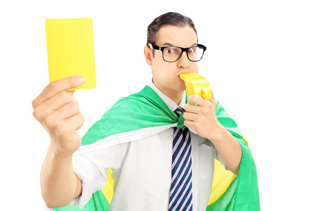 penalty flag: Male sport fan with flag of Holland holding a yellow card and blowing a whistle isolated on white