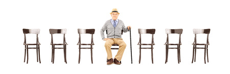 cane chair: Relaxed senior gentleman sitting on a wooden chair and looking at camera isolated on white