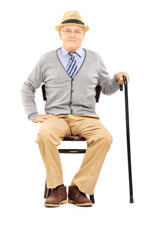 sitting chair: Relaxed senior man sitting on a wooden chair and looking at camera isolated on white