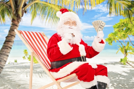Santa claus on a vacation, sitting on a beach chair with cigar and us dollars, on a tropical beach photo