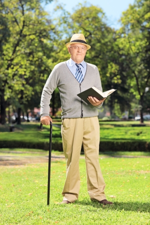 Full length portrait of a senior gentleman reading a book and looking at camera in park photo