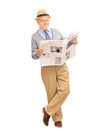 Full length portrait of a senior gentleman reading a newspaper and leaning against a wall