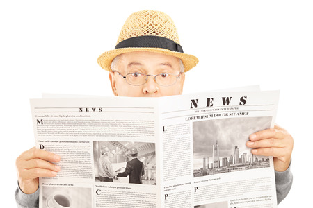shot from behind: Scared senior man with glasses hiding behind a newspaper isolated on white background