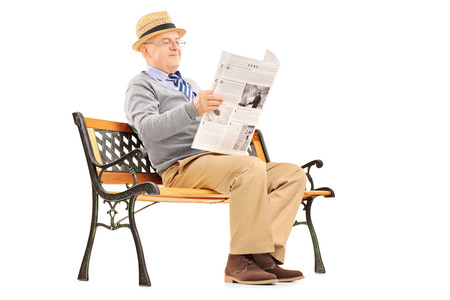 Senior gentleman reading newspaper and sitting on a wooden bench isolated on white background photo