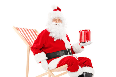 Smiling Santa Claus sitting on a beach chair and holding a gift box isolated on white background photo