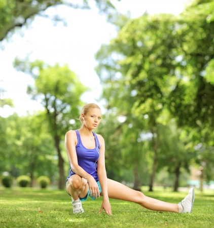 Young blond female exercising in a park on a sunny day, shot with a tilt and shift lens photo