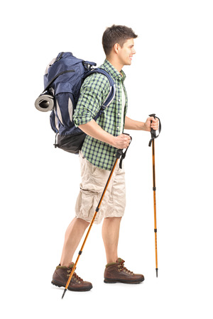 trekking pole: Full length portrait of a hiker with backpack and hiking poles walking isolated on white background