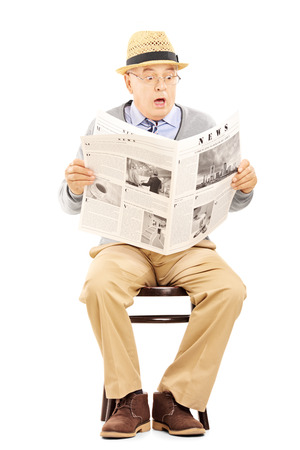 senior reading: Senior gentleman in shock on a wooden chair reading a newspaper isolated on white background Stock Photo