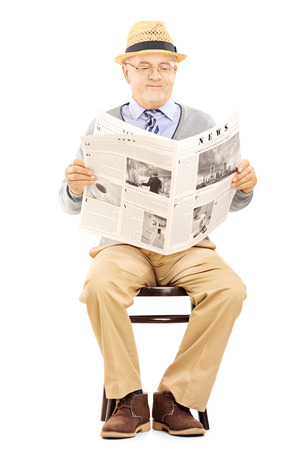 Senior gentleman reading newspaper and sitting on a wooden chair isolated on white background photo