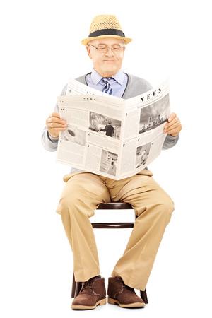 oude krant: Senior man het lezen van kranten en zittend op een houten stoel op een witte achtergrond Stockfoto