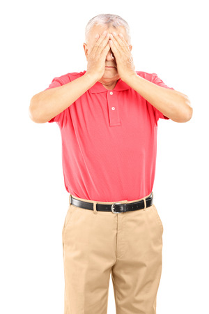 Mature man with hands over his eyes isolated on white background photo