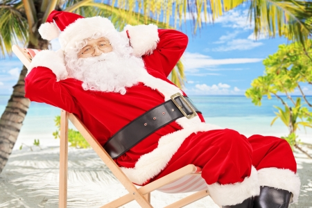 summer wear: Relaxed Santa Claus sitting on a chair, on a tropical beach with palm trees