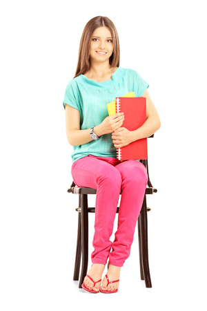 Smiling female student on a wooden chair holding books and looking at camera isolated on white background Imagens