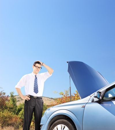 Young businessman standing near his broken car and thinking what to do, shot with a tilt and shift lens photo