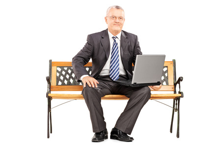 sitting on a bench: Mature professional man sitting on a wooden bench and working on a laptop isolated on white background