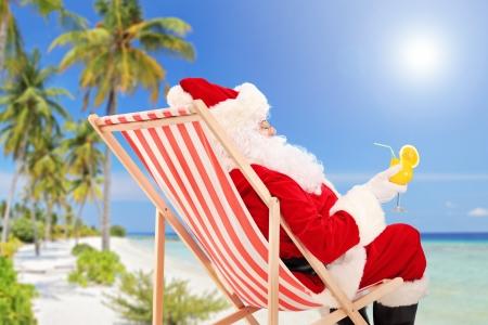 Kerstman liggend op een strandstoel en drinken sinaasappel cocktail, genieten op een zonnige dag, op een strand Stockfoto