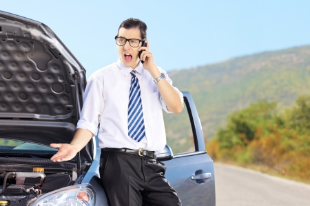 Young nervous man standing next to his broken car and talking on a mobile phone, on a sunny day photo