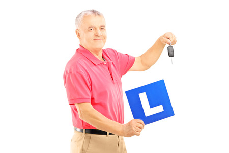l plate: Smiling senior man holding a L plate and car key isolated on white background