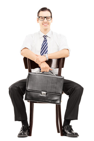Young businessman holding a leather briefcase and waiting on a wooden chair isolated on white background photo