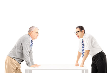 disagreeing: Angry businessman shouting at senior man isolated on white background Stock Photo