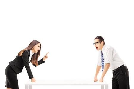 Hombre de negocios enojado gritando en empresaria que amenaza aislada en el fondo blanco
