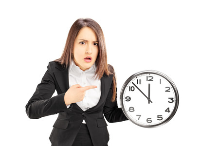 late 20s:  Angry young businesswoman pointing on a wall clock, isolated on white background