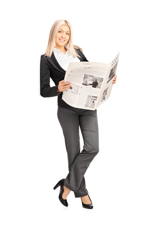 Full length portrait of a young businesswoman holding a newspaper and leaning against a wall photo