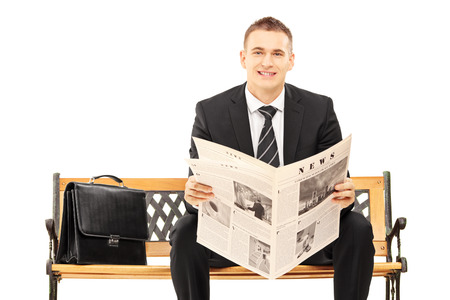 Young businessman sitting on a wooden bench with newspaper and looking at camera isolated on white background photo