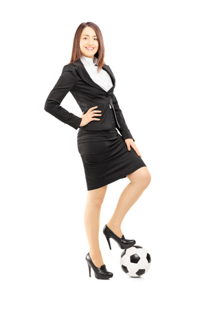 Full length portrait of a young businesswoman in high heels posing with a soccer ball isolated on white background photo
