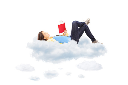novel: Young female student reading a novel and lying on clouds, isolated on white background Stock Photo