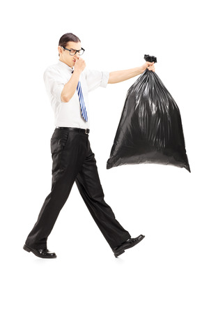 stinky: Full length portrait of a male closing his nose and carrying a stinky garbage bag isolated on white background