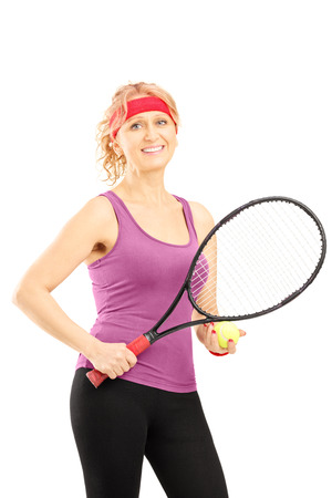 Mature female tennis player holding a racket and a ball isolated against white background photo