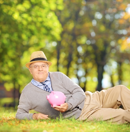 Satisfied mature gentleman in a park holding a piggy bank, shot with a tilt and shift lens photo