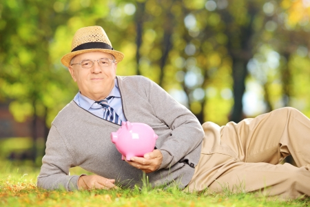 Smiling mature gentleman lying on a green grass and holding a piggy bank in a park