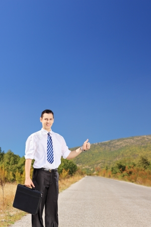 Young businessperson holding a leather suitcase and hitchhiking on a road photo